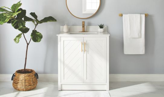 A striking gold faucet on a white single sink vanity.